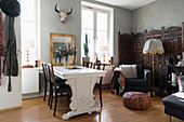 Dining table and chairs, armchair and screen in open-plan interior with pale grey walls