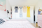 Bed and walk-in wardrobe with dresses hung on front in bedroom