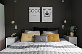 Double bed and bedside cabinets against charcoal wall in bedroom