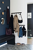 Coat rack and bench in foyer area with dark blue wall