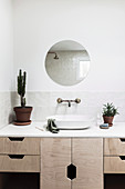Round mirror above the vanity with light wooden fronts