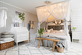 Double bed below canopy with lights, wooden bench and bureau in pale bedroom