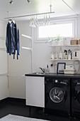 Waschmaschine und aufgehängte Kleiderstange im Waschraum