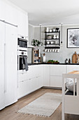 White kitchen counter with black worksurface with fitted appliances