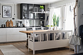 White kitchen counter with black worksurface and dining area in kitchen