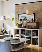 Vintage radio and houseplant on sideboard in front of old map on wall and white coffee table in living room