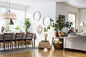 Long table and dining chairs and round mirrors on wall in airy dining area