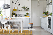 White kitchen with storage cupboards and dining area