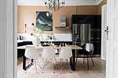 Essbereich mit weißen Klassikerstühlen, im Hintergrund Kühlschrankkombination mit Edelstahl-Türen in Wohnküche