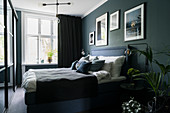 Double bed in bedroom with dark walls
