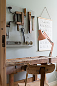 Desk made from old workbench and tools decorating wall
