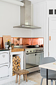 Sheet copper splashback in kitchen with wood-fired oven