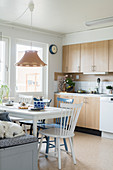 Dining table with chairs and bench in kitchen-dining room with pale cupboards