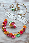 Hand-crafted garland of paper fans and bunting with lettering