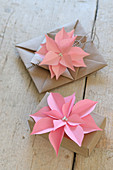 Pink paper flowers decorating wrapped gifts