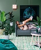 Young woman lying on green upholstered sofa in living room with house plants and green wall
