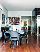 Dining area with black classic chairs, black tiled wall in the background