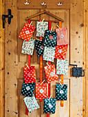 DIY-Adventskalender aus bunten Papiertüten an Holztür