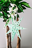 Green paper star with holes on a branch of flowers