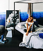 Young woman sitting on the four-poster bed in front of a two-tone wall