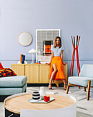 Woman leaning against sideboard in living room with designer furniture