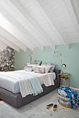 Double bed in bedroom with mint-green wall and white-painted wooden ceiling
