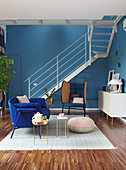 Seating and staircase in open-plan interior with blue wall