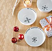 Mit Weihnachtsworten und Schneeflocken bemalten Schalen