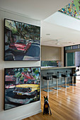 Paintings of old cars on wall of open-plan kitchen with bar stools at counter