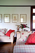Red and floral cushions on checked sofas in living room