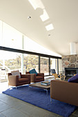 Brown sofa set, blue rug, fireplace and glass walls in lounge