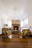 Armchairs with tartan covers, couch and coffee table in front of fireplace in living room with white-painted wood-clad walls