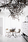 White dining room with vintage furniture and tree branch as decoration
