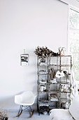 White designer rocking chair next to vintage wire shelves