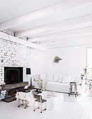 Living room in white with sofa and vintage seating around a coffee table