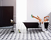 Black and white bathroom with cement tiles, woman in the bathtub