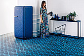 Blue tiled floor with organic pattern and blue fridge, woman at console