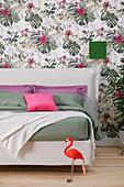 Weißes Doppelbett mit Bettkopfteil vor Tapete mit Pflanzenmotiv