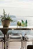 Classic chairs around metal table on balcony with sea view