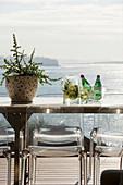 Klassikerstühle um Metalltisch auf Balkon mit Meerblick