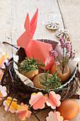 Origami-Osterhase, aus Papier gefaltet, mit selbstgemachter Girlande aus Papierblumen