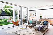 Freistehendes Sofa im offenen Wohnraum mit Zugang zum Garten