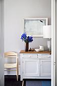 Blick durch offene Tür auf alte Kommode mit blauen Blumen