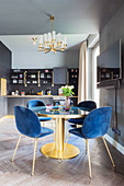 Dining table and blue velvet chairs in grey mid-century kitchen