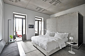 Double bed with white bed linen against concrete partition in hotel room