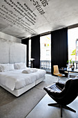 Double bed with white bed linen against concrete wall in hotel room with leather swivel armchair in foreground