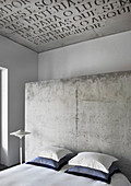 Double bed with pillows against concrete partition in hotel room with lettering on concrete ceiling