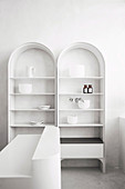Two white shelves with arches and minimalist decoration