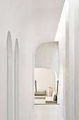 White hallway with organic shapes, arches and skylight