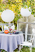 Autumnal arrangement on table below paper lanterns in garden